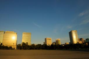 皇居前広場と夕日に輝く丸の内の高層ビル群の写真素材 [FYI03409879]