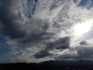 太陽を覆う雲たちと山並みの写真素材 [FYI03409945]
