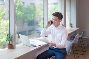 携帯電話で話す男性の写真素材 [FYI03410109]
