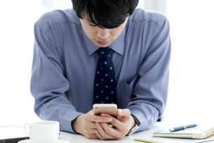 スマートフォンを見るビジネスマンの写真素材 [FYI03411027]