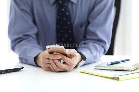 スマートフォンを持つビジネスマンの手元の写真素材 [FYI03411028]