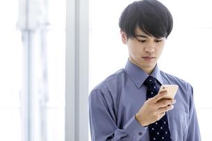 スマートフォンを見るビジネスマンの写真素材 [FYI03411029]