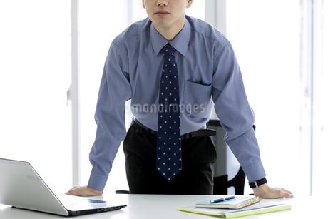 テーブルに手をつくビジネスマンの写真素材 [FYI03411032]