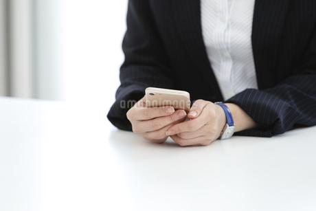 スマートフォンを持つビジネスウーマンの手元の写真素材 [FYI03411055]