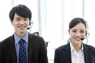 インカムをつけたビジネスマンとビジネスウーマンの写真素材 [FYI03411056]