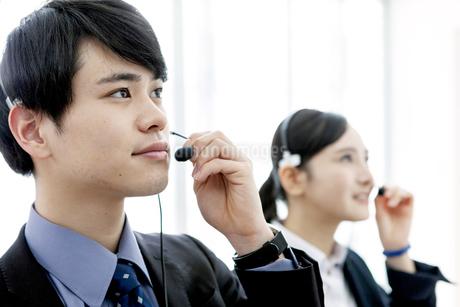 インカムをつけたビジネスマンとビジネスウーマンの写真素材 [FYI03411057]