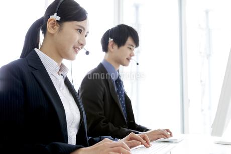 インカムをつけたビジネスマンとビジネスウーマンの写真素材 [FYI03411058]