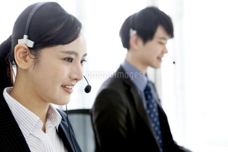 インカムをつけたビジネスマンとビジネスウーマンの写真素材 [FYI03411059]