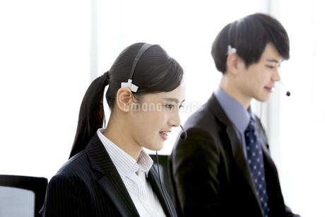 インカムをつけたビジネスマンとビジネスウーマンの写真素材 [FYI03411061]