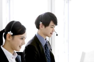 インカムをつけたビジネスマンとビジネスウーマンの写真素材 [FYI03411062]