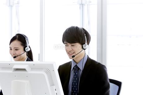 インカムをつけたビジネスマンとビジネスウーマンの写真素材 [FYI03411065]