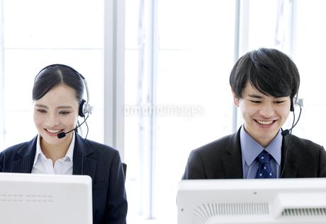 インカムをつけたビジネスマンとビジネスウーマンの写真素材 [FYI03411066]
