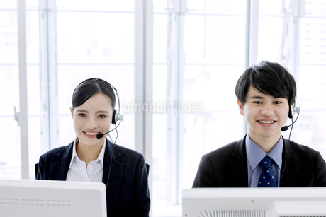 インカムをつけたビジネスマンとビジネスウーマンの写真素材 [FYI03411067]