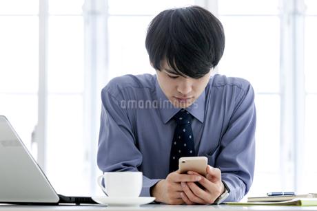 スマートフォンを見るビジネスマンの写真素材 [FYI03411079]