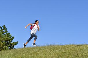 青空で走る小学生の女の子(ランドセル)の写真素材 [FYI03411342]