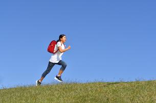 青空で走る小学生の女の子(ランドセル)の写真素材 [FYI03411343]
