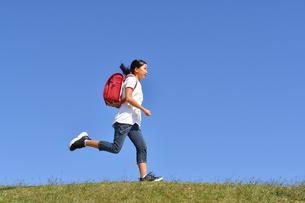 青空で走る小学生の女の子(ランドセル)の写真素材 [FYI03411346]