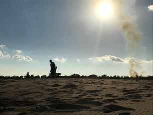 日没前の逆光を受けた土埃が舞う砂浜で遊ぶ親子の写真素材 [FYI03412172]