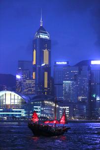 ビクトリア湾を行く観光船ジャンク・ボート「アクア・ルナ」後方は香港島の高層ビルの写真素材 [FYI03412176]