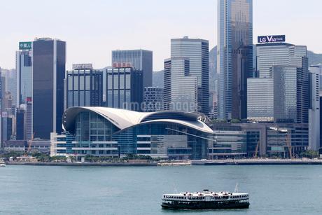 英国植民地時代から運行するスターフェリー。後方は香港返還時に作られたコンベンションセンターの写真素材 [FYI03413374]