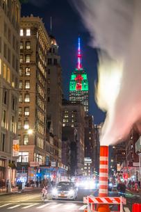 夜の五番街で街頭の灯りに照らされ漂う蒸気の下を走り抜ける車と後ろでクリスマスカラーに輝くエンパイヤーステートビルディングの写真素材 [FYI03413510]