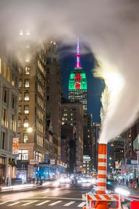 夜の五番街で街頭の灯りに照らされ漂う蒸気の下を走り抜ける車と後ろでクリスマスカラーに輝くエンパイヤーステートビルディングの写真素材 [FYI03413511]