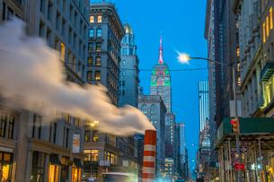 夕暮れの五番街で街頭の灯りに照らされ漂う蒸気の後ろでクリスマスカラーに輝くエンパイヤーステートビルディングの写真素材 [FYI03413577]
