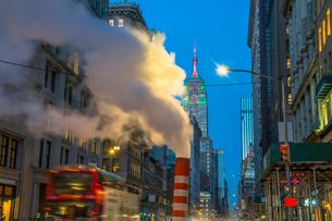 夕暮れの五番街で街頭の灯りに照らされ漂う蒸気の後ろでクリスマスカラーに輝くエンパイヤーステートビルディングの写真素材 [FYI03413580]