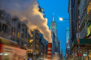 夕暮れの五番街で街頭の灯りに照らされ漂う蒸気の後ろでクリスマスカラーに輝くエンパイヤーステートビルディングの写真素材 [FYI03413582]
