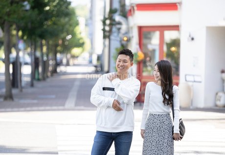 街中で仲良くデートをする若い男女の写真素材 [FYI03414227]