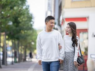 街中で仲良くデートをする若い男女の写真素材 [FYI03414229]