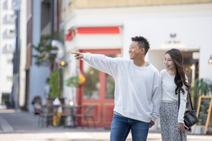 街中で仲良くデートをする若い男女の写真素材 [FYI03414233]