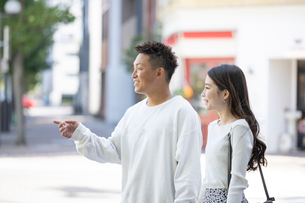 街中で仲良くデートをする若い男女の写真素材 [FYI03414234]