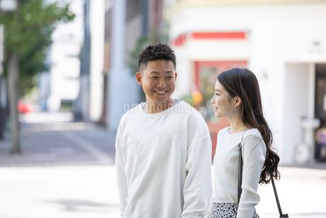 街中で仲良くデートをする若い男女の写真素材 [FYI03414235]