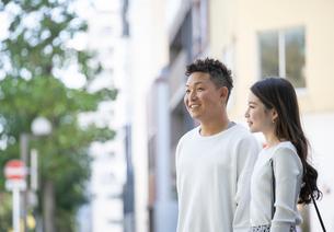 街中で仲良くデートをする若い男女の写真素材 [FYI03414237]