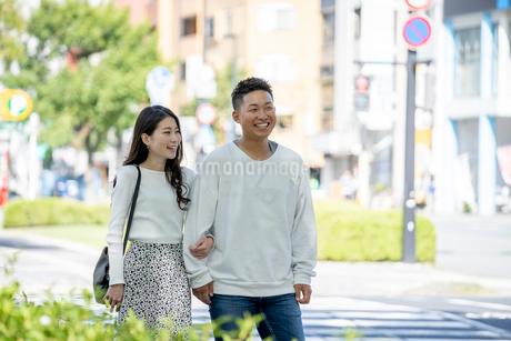 街中で仲良くデートをする若い男女の写真素材 [FYI03414240]