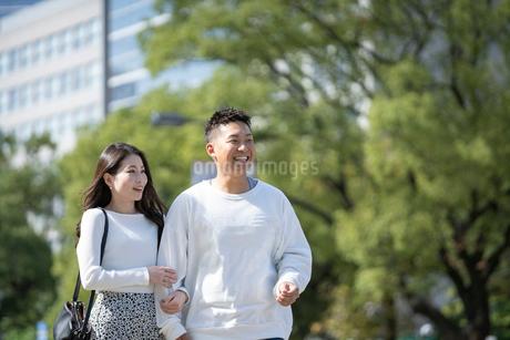 綺麗な緑を背景に仲良く歩く若い男女の写真素材 [FYI03414241]