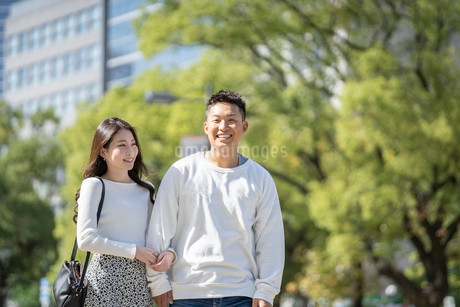 綺麗な緑を背景に仲良く歩く若い男女の写真素材 [FYI03414242]