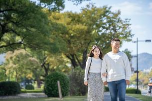 綺麗な緑を背景に仲良く歩く若い男女の写真素材 [FYI03414243]