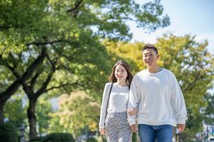 綺麗な緑を背景に仲良く歩く若い男女の写真素材 [FYI03414244]