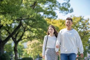 綺麗な緑を背景に仲良く歩く若い男女の写真素材 [FYI03414245]