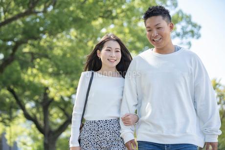 綺麗な緑を背景に仲良く歩く若い男女の写真素材 [FYI03414246]