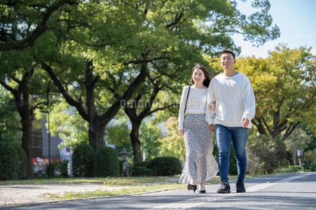 綺麗な緑を背景に仲良く歩く若い男女の写真素材 [FYI03414247]