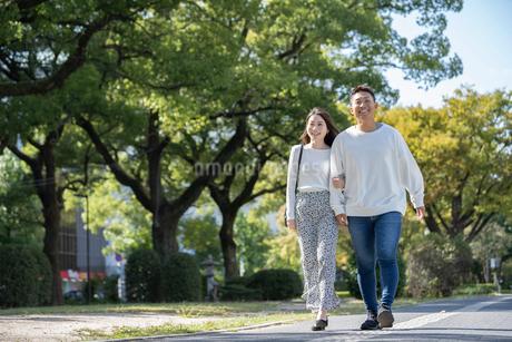 綺麗な緑を背景に仲良く歩く若い男女の写真素材 [FYI03414248]