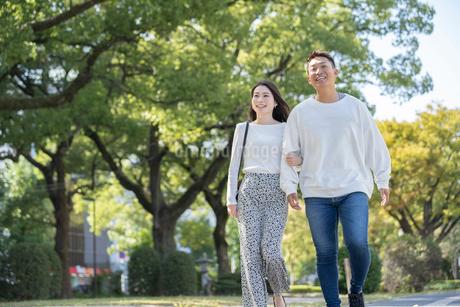 綺麗な緑を背景に仲良く歩く若い男女の写真素材 [FYI03414249]