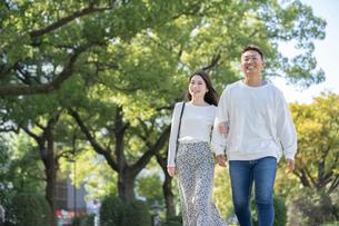 綺麗な緑を背景に仲良く歩く若い男女の写真素材 [FYI03414250]