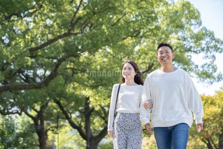 綺麗な緑を背景に仲良く歩く若い男女の写真素材 [FYI03414251]