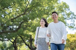 綺麗な緑を背景に仲良く歩く若い男女の写真素材 [FYI03414252]