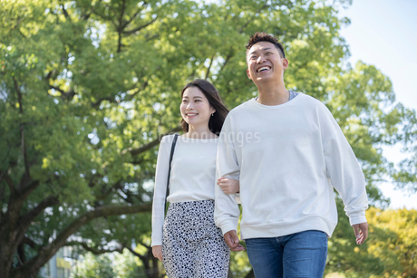 綺麗な緑を背景に仲良く歩く若い男女の写真素材 [FYI03414253]