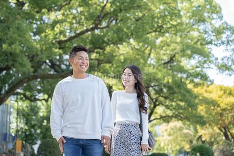綺麗な緑を背景に仲良く歩く若い男女の写真素材 [FYI03414254]